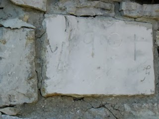 "Cornerstone on the old barn, marked ""1901"" with what appears to be the letter ""J"""
