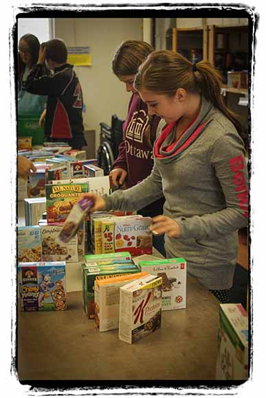 Stittsville Food Bank volunteers, including Kayla Robinson help organize donations. Photo by Barry Gray.