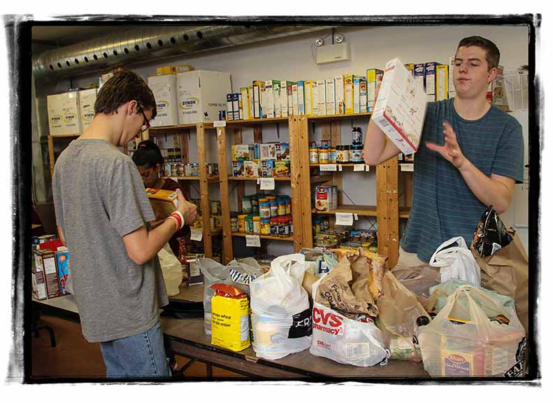 Stittsville Food Bank volunteers Adam McCaw, Quentin Pickett check expiry dates on donations. Photo by Barry Gray.