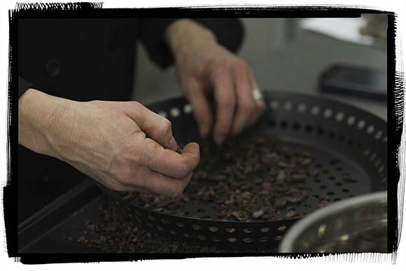 Roasted beans being hand separtated from shells after being roasted.