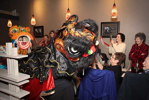 Two of the three lions dance among diners. Photo by Barry Gray