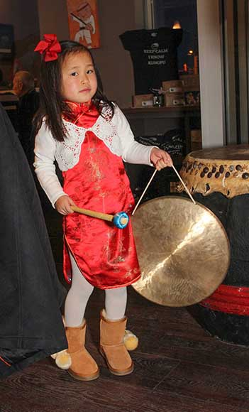 Seven year old Keira Southern holds the gong and helps drum in the lions for the Chinese New Year celebrations at Kungfu Bistro. Photo by Barry Gray.