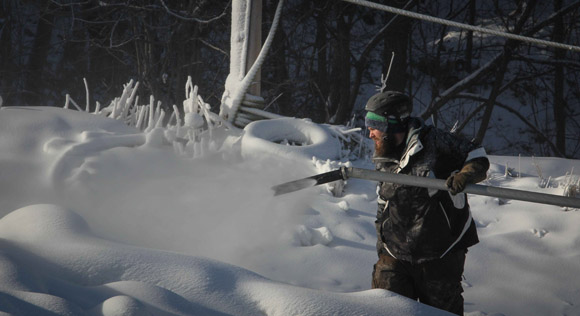 Alex Weir adjusts the snow gun near the top of  a trail.