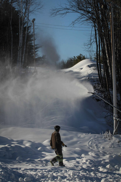 Workers move snow guns to help cover the trails at Mount Pakenham.