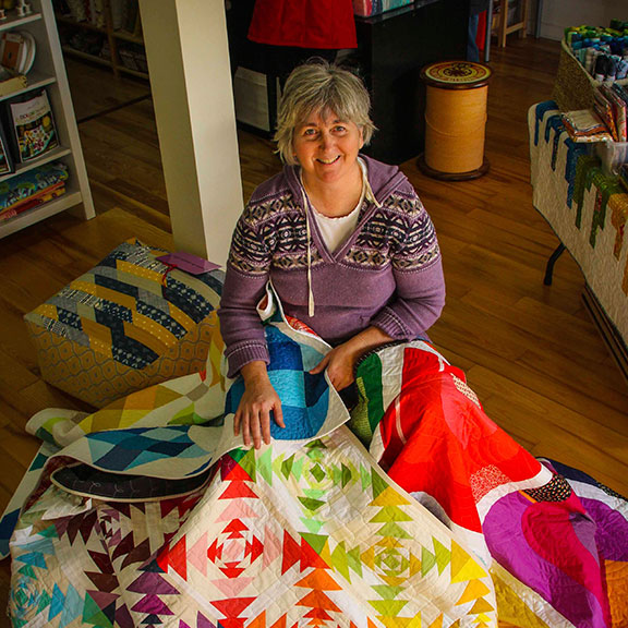 Pam Denesyk with some award winning quilts in her Mad About Patchwork store. (Photo by Barry Gray)