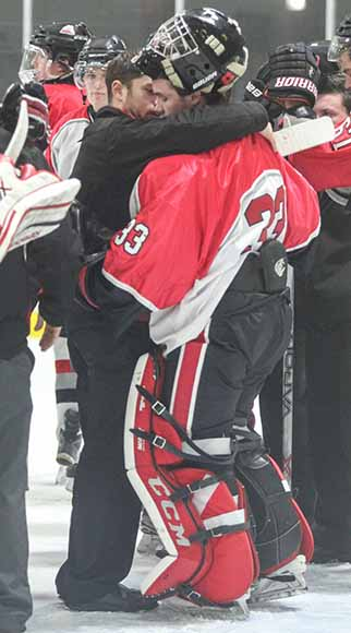 Stittsville Rams goalie Matt Couvrette is consoled by coaching staff.