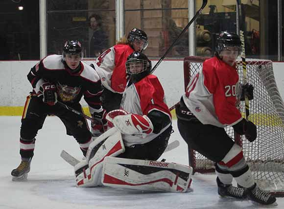 Rams goalie Connor Ellis watches the puck deflect off Rams player Connor Cobbold early in the  first period.