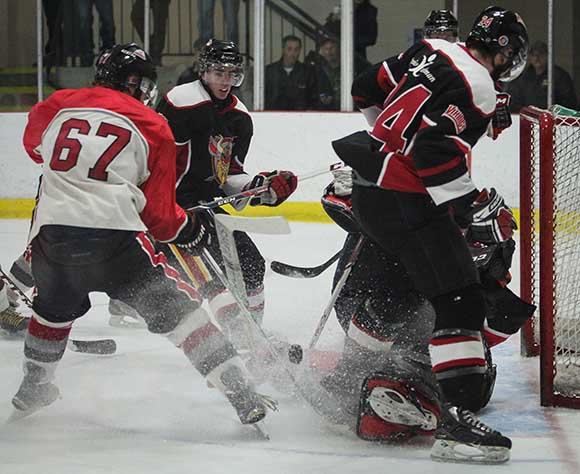 Stittsville Rams goalie Matt Couvrette makes a save on Casselman Vikings Thierry Henry as Rams Mitch Kerwin helps clear the puck.  Photo by Barry Gray.