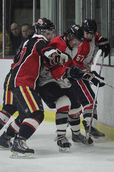 Casselman Vikings and Stittsville Rams players battle against the boards.    Photo by Barry Gray.