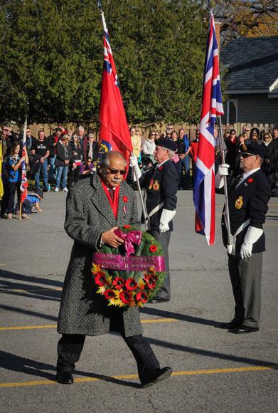 City Councillor Shad Qardi walks to lay a wreath. Photo by Barry Gray