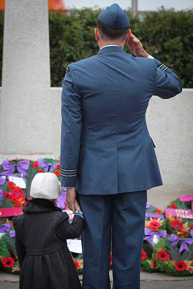A veteran and his daughter take a moment to salute after the ceremonies have concluded.