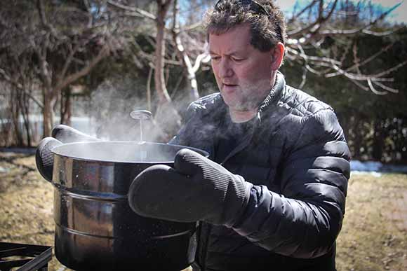 Caughey moves boiling pots across his yard.