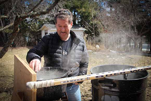 Caughey monitors the temperatures on both pots of maple sap
