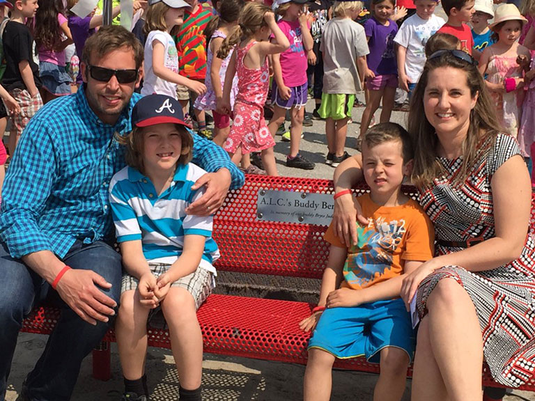 The Jude family, left to right: Steve, Mason (8), Colby (6) and Dev. They're sitting on a Buddy Bench at A. Lorne Cassidy elementary school named in memory of Bryce Jude, who passed away in 2012 after a battle with leukemia. Photo via A. Lorne Cassidy School.