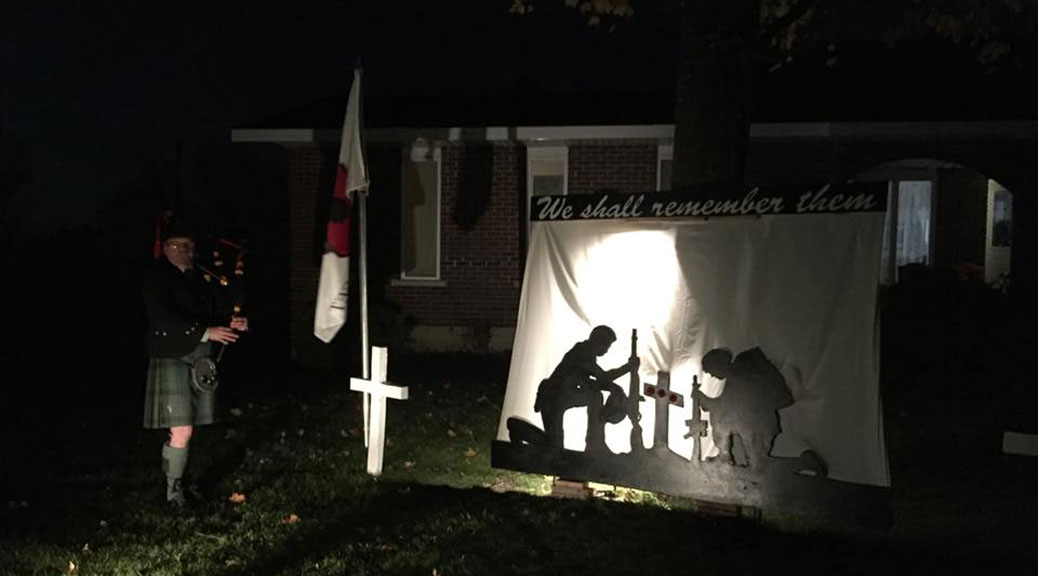 A bagpiper plays in front of a backlt Remembrance Day display in front of Dennis Burton's home on Flewellyn Road.