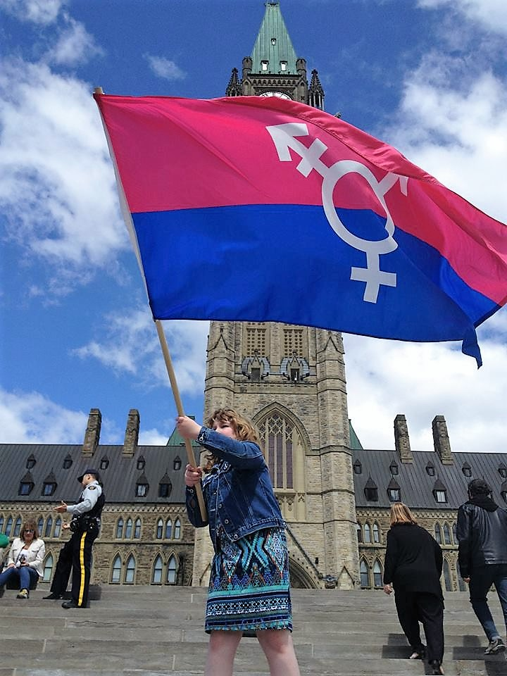 Charlie Lowthian-Rickert flies the pride flag on Parliament Hill.