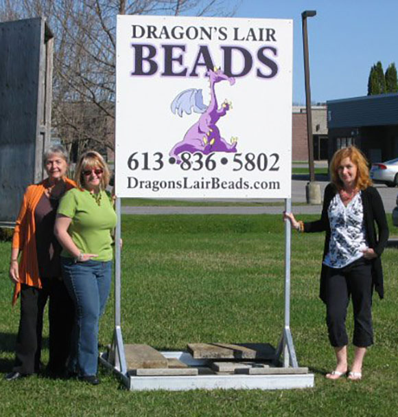 Maureen Green, along with owners Vicki Green and Nicola Shute pose with the Lair's new sign in May 2001. (via Facebook)