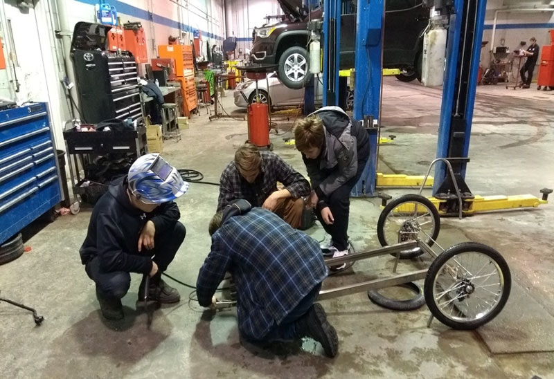 The EV Pioneers fabrication team hard at work welding the frame of the EV.
