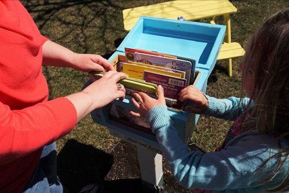 Amanda and Maëlle opening their Little Free Library to search for new books. Photo by Christine Vezarov.