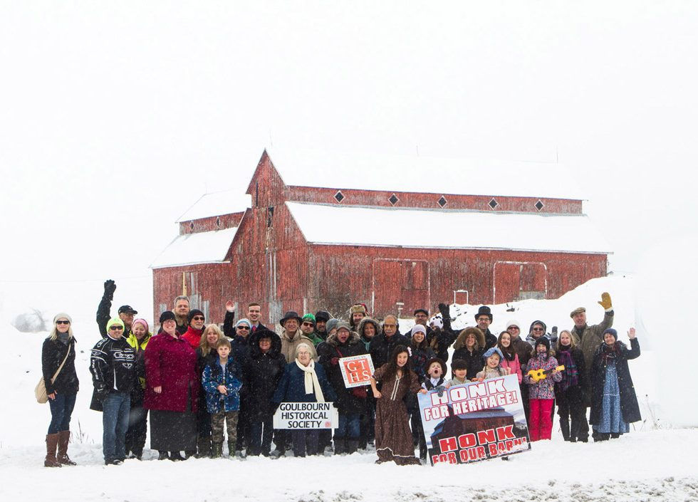 Friends of the Bradley-Craig Farm assemble for a photo in front of the landmark red barn on February 4, 2018. Photo by Rob Hambly.
