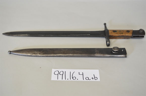 German Bayonet  (a) Dark metal sheath with rounded, circular point and additional rounded attachments on the underside to fit the bayonet. (b) Long narrow blade with wood-inset handle, small attachments on the underside of the guard with circular slots.
