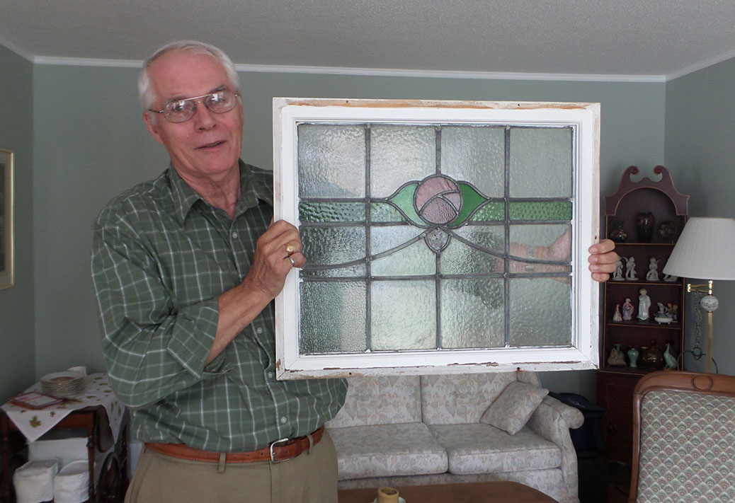 Gordon Walt holds a stained glass window that  was salvaged from their home before it was torn down earlier in August.  The window was reclaimed from a home in the Glebe, and used in their bathroom.