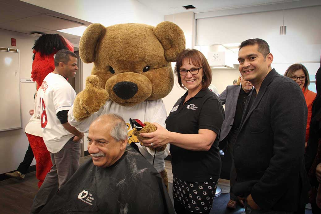 Stittsville councillor Shad Qadri gets his hair cut by Hair Donation Ottawa CEO Helene Hutchings at the annual event held at Algonquin College. The CHEO Bear and CHEO Community Engagement Officer Bob Ghosh look on. This year's donations totalled over $100,000. Photo by Barry Gray.