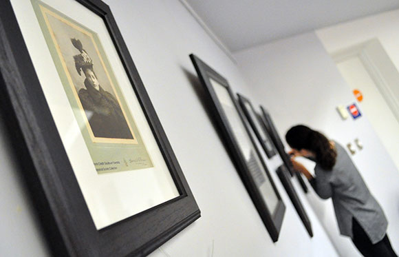 Sarah Allen hangs photographs that show how hat fashions have changed over the years. Photo via the Goulbourn Museum.
