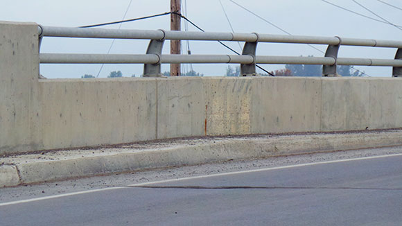 On the west side of the bridge, there's a narrow curb less than a foot wide.
