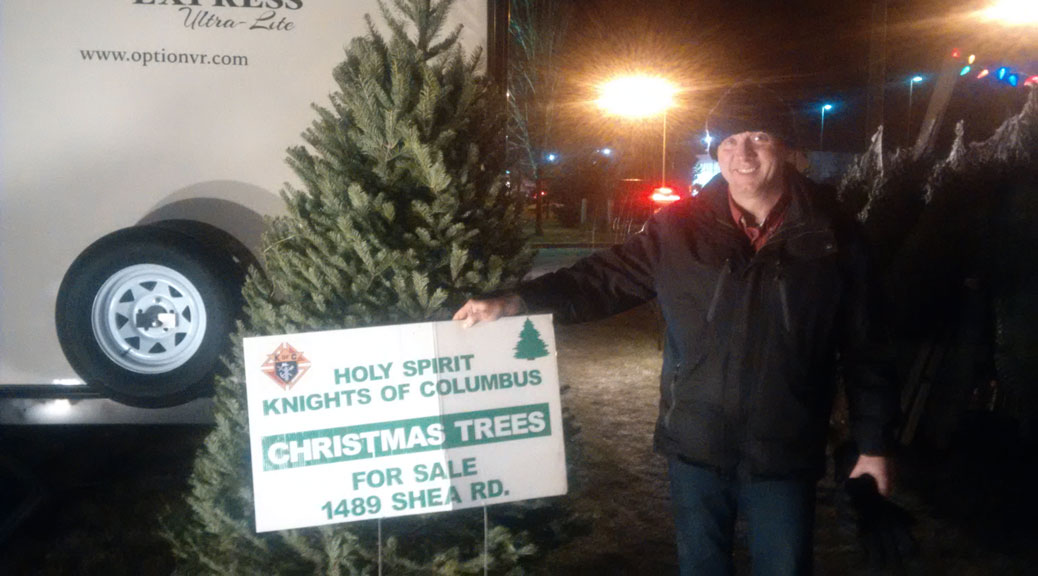 Knights of Columbus volunteer David Hatch, with one of the 8-foot balsam firs for sale.
