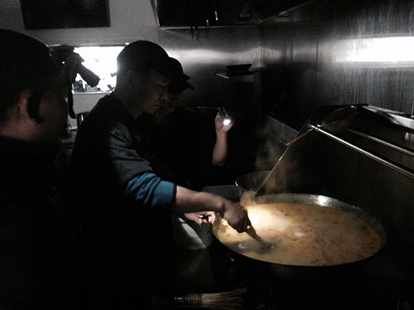 Staff at Kungfu Bistro cook soup by flashlight.