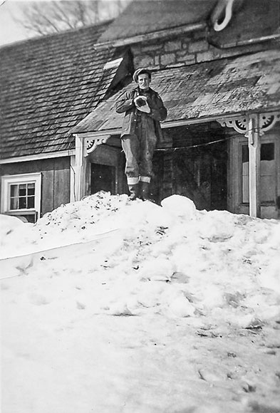 Lyman Boyd at south side of farm house, showing how much snow there was, 1940s. Photo courtesy of Melodie McCullough.