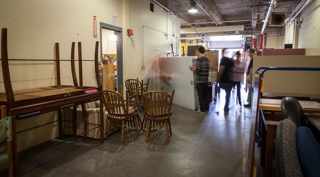 Volunteers move and sort donated furniture in the Matthew House warehouse. Photo via Matthew House
