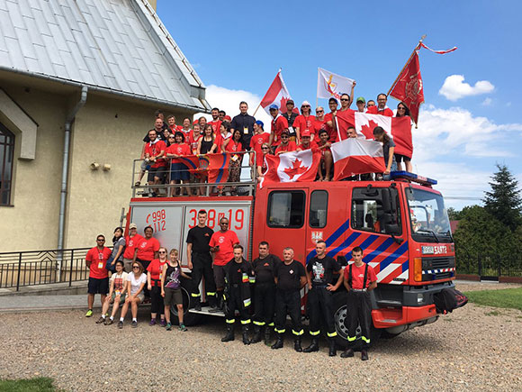 "A fire truck in Krakow: ""The fire crew there very generously drove us to a few locations when we needed to move the group! I am in the navy shirt in the centre, top row. My sister is holding the Canada flag on the left hand side of the image, in sunglasses."""
