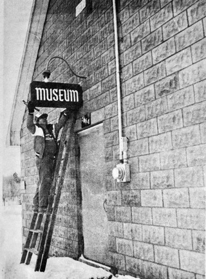 "Newspaper from 1990 showing the original ""Museum"" sign being tested out on the building.  In the photo, John Leroux of the Goulbourn Parks Department is pictured trying out the sign which was made and donated by Claude Swolfs of Stittsville. Alternations were made to the lighting over the door before permanently installing the sign."