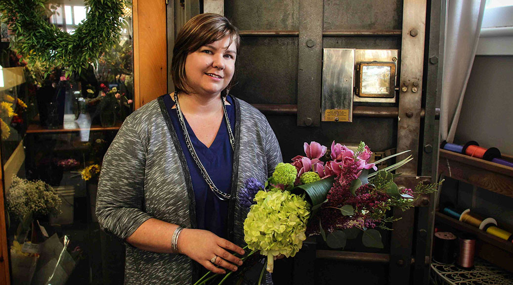 Pretty Pots owner Shannon Gorman, in front of the flower cooler that was once a bank vault. Photo by Barry Gray.