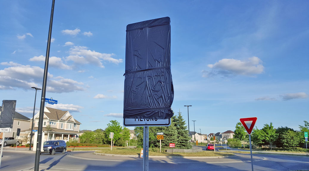 "The City will be adding even more signage to roundabouts as part of their new PXO or ""Pedestrian Crossover"" program. The signs are up at Huntmar-Rosehill, waiting to be unveiled later this month."