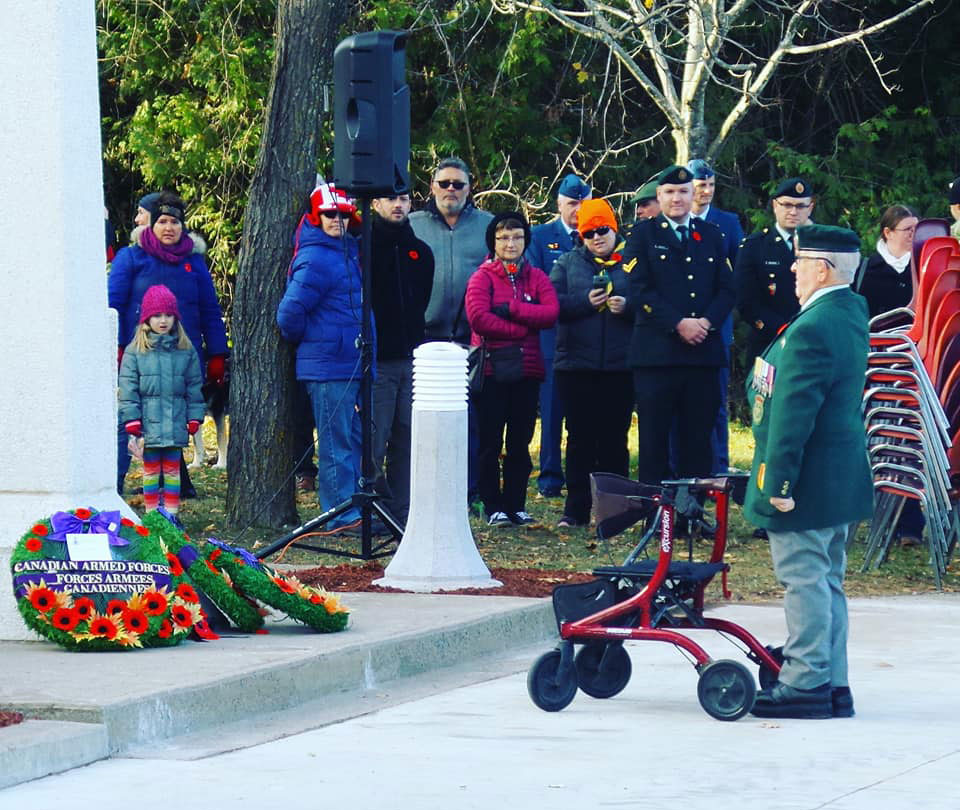 Johnny Leroux, a Korean War veteran, places a wreath at the cenotaph. The Remembrance Day ceremony is held in front of the hockey arena named after Leroux. Photo by G. Gower.