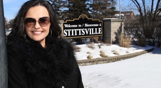 Sandra Plagakis, morning host on KiSS 105.3 in Ottawa, stands in front of the Stittsville sign