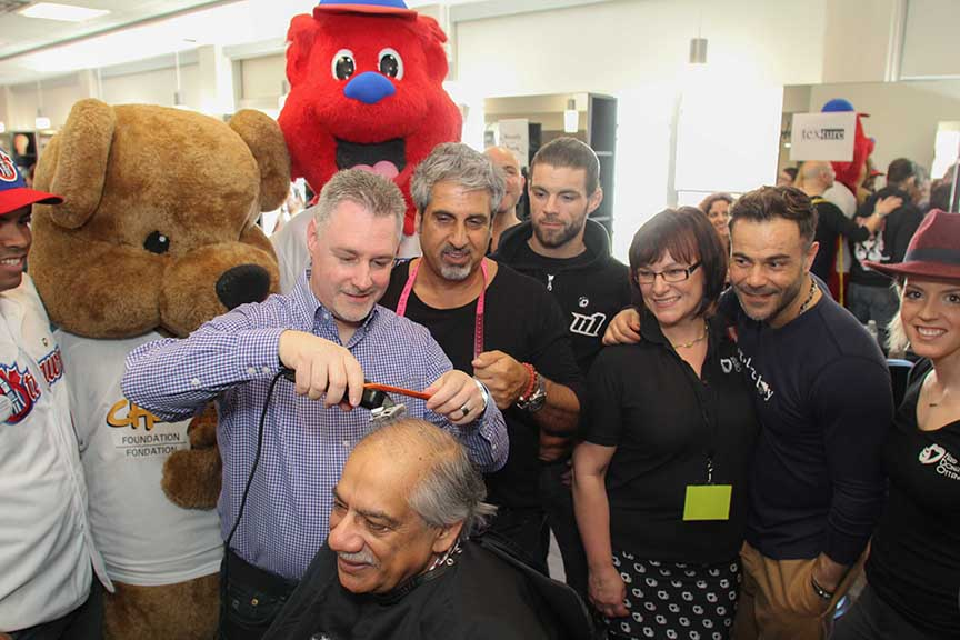Deputy Mayor Mark Taylor cuts Ward 6 Councillor Shad Qadri at the annual HairDonation Ottawa event at Algonquin College. Looking on are stylist Eli Saikaley and HairDonation Ottawa founder Helen Hutchings (glasses). Barry Gray (StittsvilleCentral)