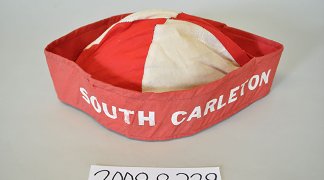 "South Carleton Beanie: One fabric beenie, red and white cap, stiffened rim with ""South Carleton"" written in white capital letters."