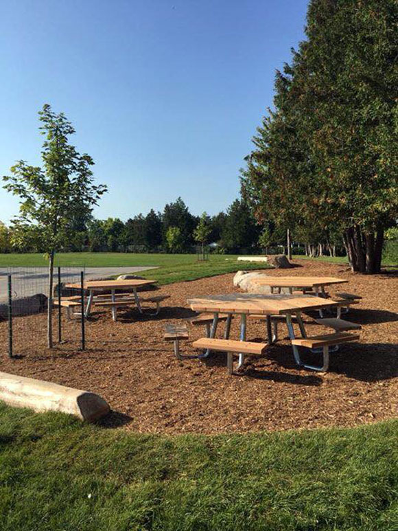 The classroom is a landscaped area behind the school with trees, rocks a log bench and three hexagon picnic tables. It's fully accessible and is already being used as a learning and play area for students and teachers. Photo by Michelle Legault.
