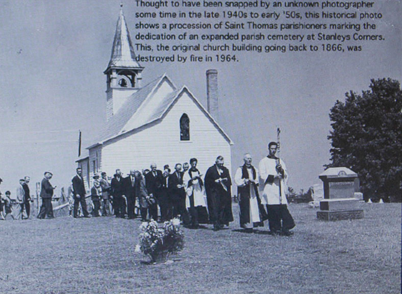 Thought to have been snapped by an unknown photographer sometime in the late 1940s to early 1950s, this historical photo shows a procession of Saint Thomas parishioners marking the dedication of an expanded parish cemetery at Stanley's Corners. This original church building dates back to 1866 and was destroyed by fire in 1964.
