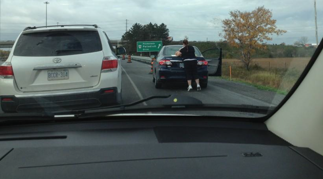 An unidentified woman changes a diaper while parked on the side of the Queensway, en route to Tanger Outlets on opening day. Photo via @PaulaMcCooey on Twitter.