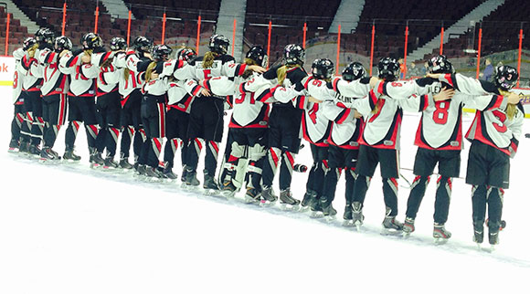 The team stands arm-in arm and sing O Canada after their win.