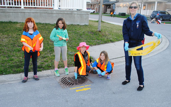 Brownies paint yellow fish stencils in the Fairwinds neighbourhood. Photo via Kerry Reimer